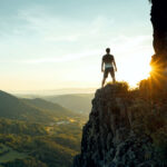 A photo of a man standing on the edge of a cliff looking out at a sunrise.