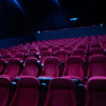 A photo showing an entirely empty movie theater with many rows of seats.