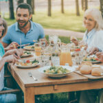 A photo of a family enjoying a meal together at an outside table.
