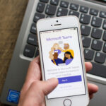 A photo showing a hand holding an iPhone with the Microsoft Teams app open.