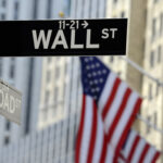 A photo of a street sign for Wall Street with the American flag in the background.