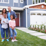 A Black family stands in front of their home
