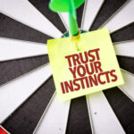 """A photo showing a dartboard with a dart through the bull's-eye and a sticky note reading """"Trust Your Instincts."""""""