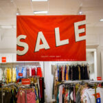 "A ""sale"" sign hangs above a clothing store"