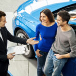 A photo showing a salesman at a car dealership talking to a young couple.