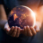 A person holds the globe in their hands