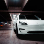 A white Tesla parked in a shadowy garage