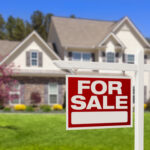 """A home with a """"for sale"""" sign in the front yard"""