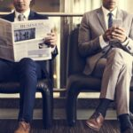Two businessmen sit and read the news