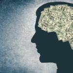 The outline of a person's head with money on the brain
