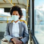 A woman wears a mask while riding the bus