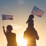 A family waves American flags in the sunset