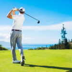 A golfer hits the ball with his club