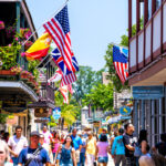 A photo showing a busy street full of shoppers lined with many businesses displaying American flags.