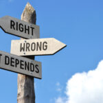 """An image of a wooden signpost against a blue sky reading """"Right, Wrong, It Depends."""""""