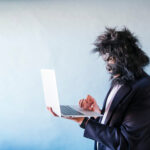 A photo of a man wearing a gorilla mask typing on a laptop.
