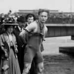 A black-and-white photo of Harry Houdini standing on the Harvard Bridge locked in chains and surrounded by onlookers.