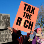 """A photo of protesters at a rally showing one protester holding a """"Tax the Rich"""" sign."""