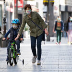 A photo showing a mother helping her son, both wearing masks, ride his bike down a commercial street.