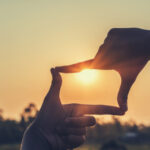 A photo of a person's hands making a rectangle in front of a sunset.