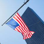 A photo of an American flag blowing in the wind in front of tall skyscrapers.