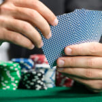 A photo showing a man's hands holding his poker cards with many poker chips in front of him.