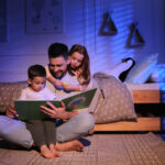 A photo showing a young father reading a bedtime story to his son and daughter.