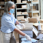A photo showing a mature woman working in a warehouse packing donations.