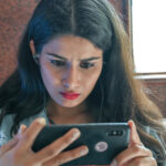 A photo of a young woman with a worried look on her face as she watches a video on her mobile phone.